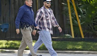 ** FILE ** George Zimmerman (right) is escorted to a home by a Lake Mary police officer on Sept. 9, 2013, in Lake Mary, Fla., after a domestic incident in the neighborhood where Zimmerman and his wife Shellie had lived during his murder trial. Zimmerman was recently found not guilty for the 2012 shooting death of Trayvon Martin. (Associated Press)