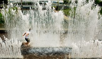 **FILE** A child cools off in the fountains at Yards Park on the Southwest waterfront (Andrew Harnik/The Washington Times)