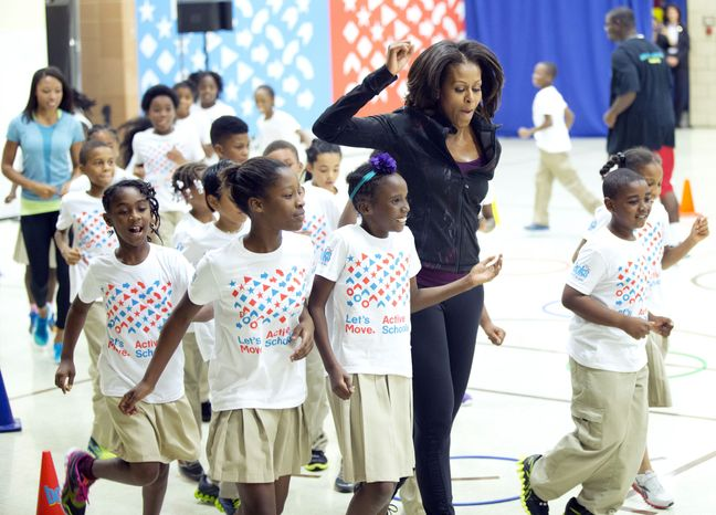 ** FILE ** First lady Michelle Obama joins exercises with pupils at Orr Elementary in Washington, Friday, Sept. 6, 2013, during a visit for a back to school event highlighting healthy changes happening in schools and across the country. (AP Photo/Manuel Balce Ceneta)