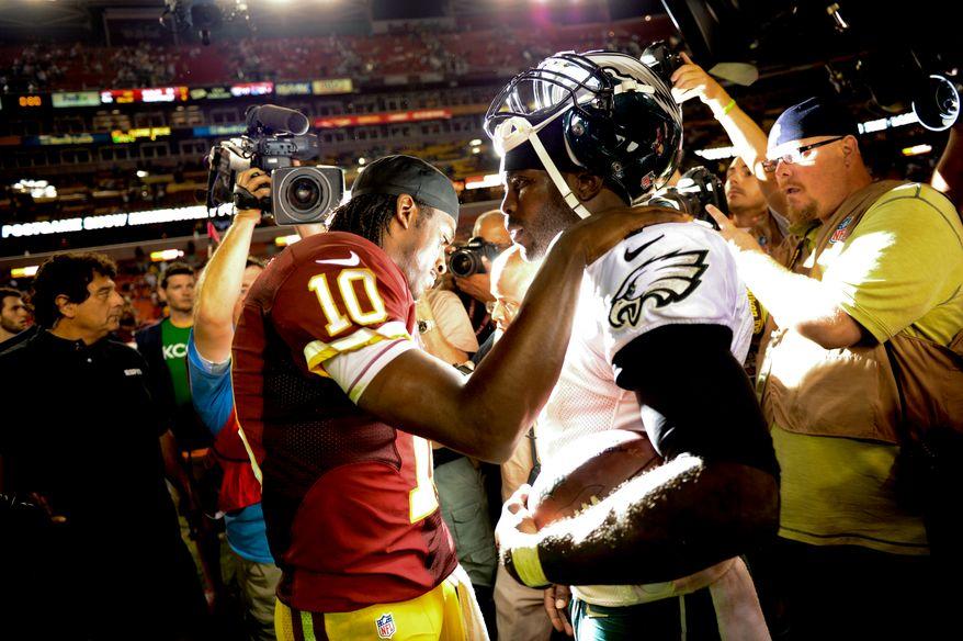 Washington Redskins quarterback Robert Griffin III (10) talks with Philadelphia Eagles quarterback Michael Vick (7) after the Washington Redskins lose to the Philadelphia Eagles 33-27 in Monday Night NFL football at FedExField, Landover, Md., Monday, September 9, 2013. (Andrew Harnik/The Washington Times)