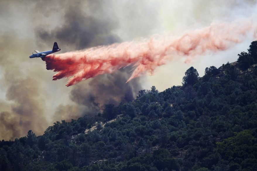A bomber drops retardant on a wildfire in Mount Diablo State Park on Monday, Sept. 9, 2013, in Contra Costa County, Calif. The blaze forced dozens of residents and animals to evacuate Monday. (AP Photo/Marcio Jose Sanchez)