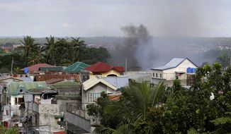 Smoke rises from a neighborhood where about 200 Muslim rebels, enraged by a broken peace deal with the Philippine government, are believed to be holding scores of hostages as human shields at the southern port city of Zamboanga, in southern Philippines for the second day, Tuesday, Sept. 10, 2013. (AP Photo/Bullit Marquez)