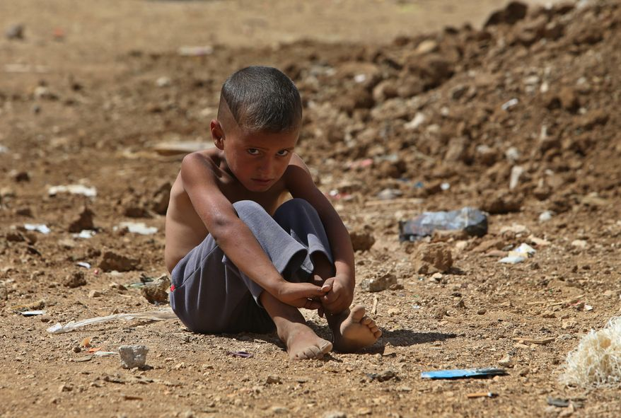 A Syrian refugee sits on the ground at a temporary refugee camp in the eastern Lebanese Town of Al-Faour, Bekaa valley near the border with Syria, on Sept. 11, 2013. Lebanon is a tiny country that shares a porous border with Syria, and has seen cross-border shelling, sectarian clashes and car bombings in recent months related to the civil war raging next door. The country of 4.5 million already is already host to nearly 1 million Syrian refugees. (Associated Press)