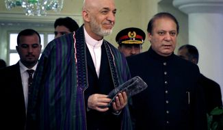 Afghan President Hamid Karzai, center left, and Pakistani Prime Minister Nawaz Sharif, right arrive for a meeting in Islamabad, Pakistan, Monday, Aug. 26, 2013. Afghanistan's president urged neighboring Pakistan to facilitate peace talks with the Taliban during a visit to Islamabad on Monday, but expectations were low in both countries that much progress would be made in jump-starting negotiations. (AP Photo/Anjum Naveed)