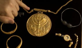Jewelry and a gold medallion with the Jewish menorah symbol etched into it is shown during a press conference at the Hebrew University in Jerusalem, Monday, Sept. 9, 2013. An Israeli archaeologist says she has uncovered a rare trove of ancient coins and medallions near Jerusalem's Temple Mount. (AP Photo/Sebastian Scheiner)