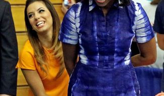 First lady Michelle Obama is joined by actress Eva Longoria at Watertown High School in Watertown, Wis. on Thursday at an event to encourage people to drink more water. Her claim that it increases energy raised eyebrows. (ASSOCIATED PRESS)