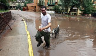 ** FILE ** In the rain, Jeff Pinkerton leads his dog Totoma across a flooded street, in Manitou Springs, Colo., Tuesday Aug. 13, 2013. Daily rainstorms have prompted new flash flood worries in Manitou Springs, which lies in the drainage of the area burned in last year's Waldo Canyon Fire. (AP Photo/Brennan Linsley)