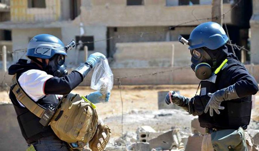 Members of a U.N. investigation team take samples from sand near a part of a missile that is likely to be a chemical-weapons rocket, according to activists, in the Damascus countryside of Ain Terma, Syria, on Wednesday, Aug. 28, 2013. (AP Photo/United Media Office of Arbeen) ** FILE **