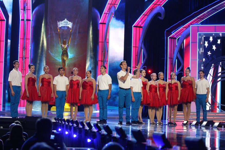 """Spotlight Performers Show Choir from the Greater Ocean City Theatre Company perform, """"God Bless the USA"""" during the Miss America preliminary competition on Wednesday, Sept. 11, 2013, in Atlantic City, N.Y. The program began after a moment of silence for the victims of the Sept. 11, 2001 attacks. (AP Photo/The Press of Atlantic City, Edward Lea)"""