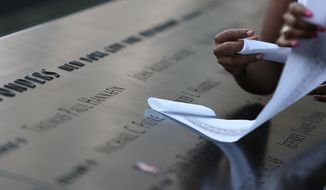 Lengths of paper are rolled up after etching names at the south tower of the September 11 Memorial during ceremonies marking the 12th anniversary of the terrorist attacks on the World Trade Center in New York, Wednesday, Sept. 11, 2013 (AP Photo/Chris Pedota, Pool)
