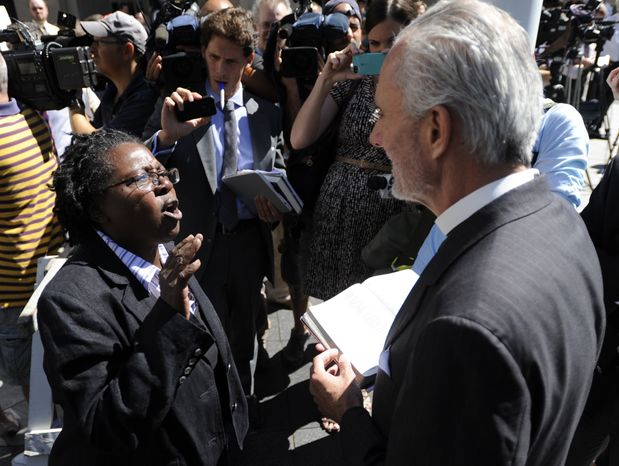 ** FILE ** Stephanie Denise-Carter, left, a supporter of gay marriages, argues with Pastor Bill Devlin, right, outside the Pennsylvania Judicial Center following the hearing of Montgomery County Clerk Bruce Hanes issuing same-sex marriage licenses Wednesday, Sept. 4, 2013, in Harrisburg, Pa. (AP Photo/Bradley C Bower)