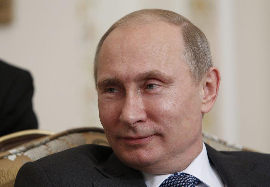 ** FILE ** Russian President Vladimir Putin smiles at the Novo-Ogaryovo state residence outside Moscow on Sept. 12, 2013. (Associated Press)