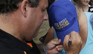 "New Jersey Gov. Chris Christie (left) signs a hat reading ""New Jersey stronger than the storm"" worn by Linda Batcho, of Seaside Park, N.J., on Sept. 13, 2013, as the governor visited the are where a day earlier a massive fire burned a large portion of the Seaside Park boardwalk in Seaside Park, N.J. The fire, which apparently started in an ice cream shop and spread several blocks, hit the recently repaired boardwalk, which was damaged last year by Superstorm Sandy. (Associated Press)"