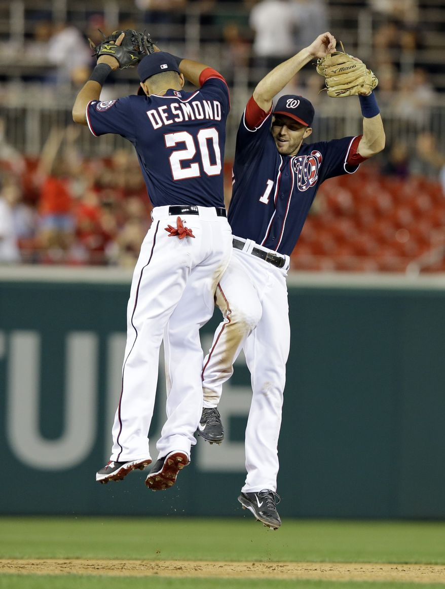 Washington Nationals shortstop Ian Desmond and second baseman Steve Lombardozzi celebrate after the Nationals beat the Philadelphia Phillies 6-1. (Associated Press photo)