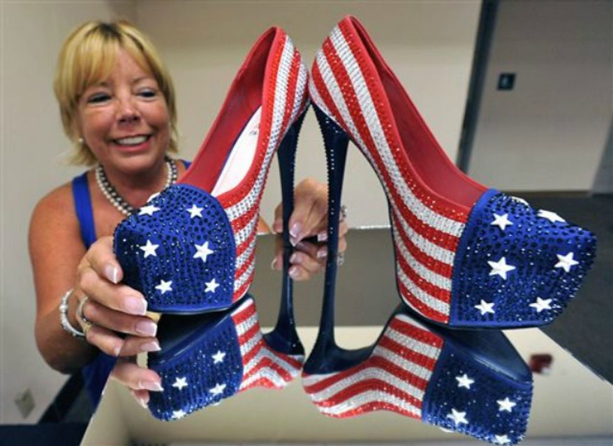"""Miss America volunteer Fran McManus, looks at the shoes Miss Pennsylvania Annie Rosellini's will wear in the 2014 Miss America pageant's """"show us your shoes"""" parade, at Boardwalk Hall, on Tuesday, Sept. 10, 2013, in Atlantic City, N.J. (AP Photo/The Press of Atlantic City, Michael Ein)"""