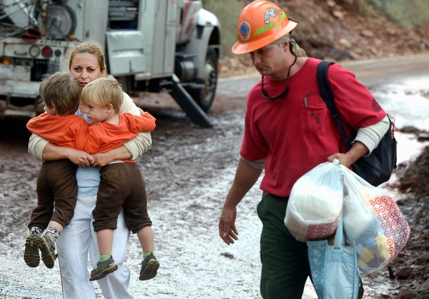 A woman, who asked not to be identified, carries two children while being evacuated by the Juniper Valley Fire Crew on Saturday on Olde Stage Road in Boulder, Colo. Rescuers rushed by land and by air to evacuate Coloradans stranded by epic mountain flooding. At least six people have been confirmed dead.