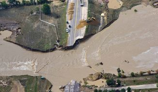 A road crew works on a stretch of highway washed out by flooding along the South Platte River in Weld County, Colorado, near Greeley, on Saturday, Sept. 14, 2013. (AP Photo/John Wark)