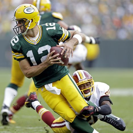 Washington Redskins' Josh Wilson sacks Green Bay Packers quarterback Aaron Rodgers during the second half of an NFL football game Sunday, Sept. 15, 2013, in Green Bay, Wis. (AP Photo/Tom Lynn)