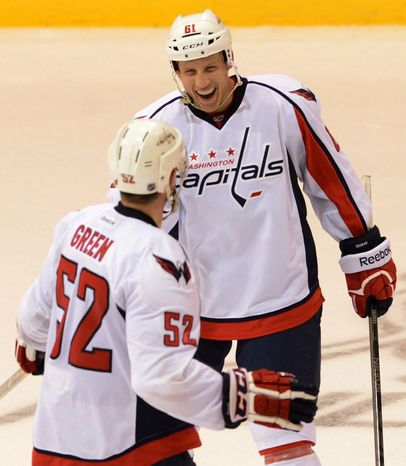 Washington Capitals' Mike Green skates toward teammate Steven Oleksy as he celebrates his game-winning shootout goal against the Winnipeg Jets to win 4-3 preseason NHL hockey game on Saturday, Sept. 14, 2013, in Belleville, Ontario. (AP Photo/The Canadian Press, Sean Kilpatrick)