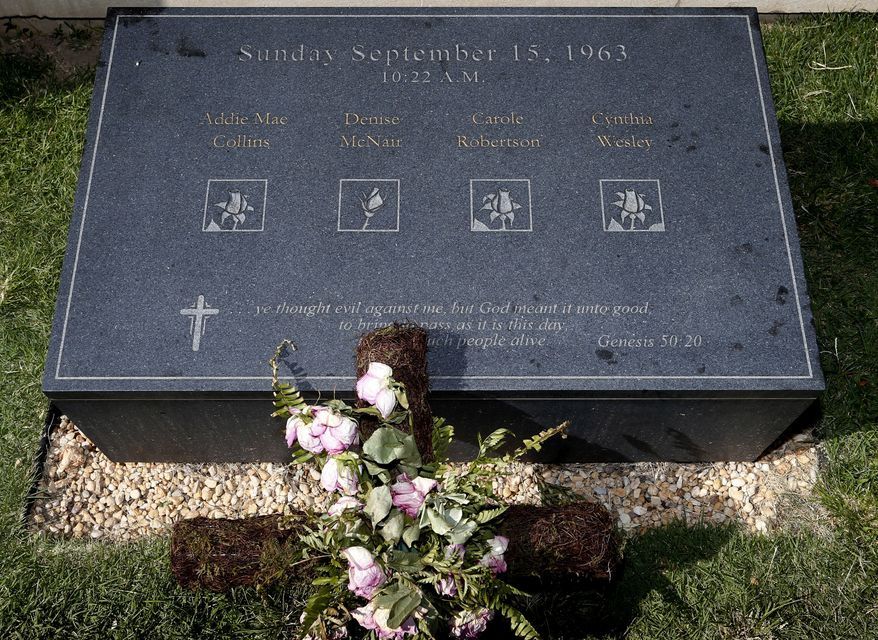 On Sunday, Sept. 15, 2013, a cross with roses sits on the marker commemorating the spot where a bomb was detonated 50 years ago by the Ku Klux Klan, killing four young girls at the 16th Street Baptist Church in Birmingham, Ala. (AP Photo/Hal Yeager)