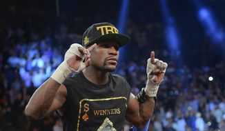 Floyd Mayweather Jr. celebrates after defeating Canelo Alvarez during a 152-pound title fight, Saturday, Sept. 14, 2013, in Las Vegas. (AP Photo/Mark J. Terrill)
