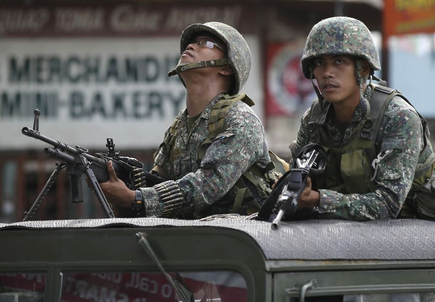 Government troopers inspect their surroundings during the continuing standoff with Muslim rebels on Sunday, Sept. 15, 2013, in Zamboanga city in the southern Philippines. The standoff, which began Monday when about 200 Moro National Liberation Front guerrillas stormed several coastal communities in Zamboanga city and seized several residents, has displaced more than 60,000, forced the closure of businesses and resulted in more than 50 deaths so far. (AP Photo/Bullit Marquez)