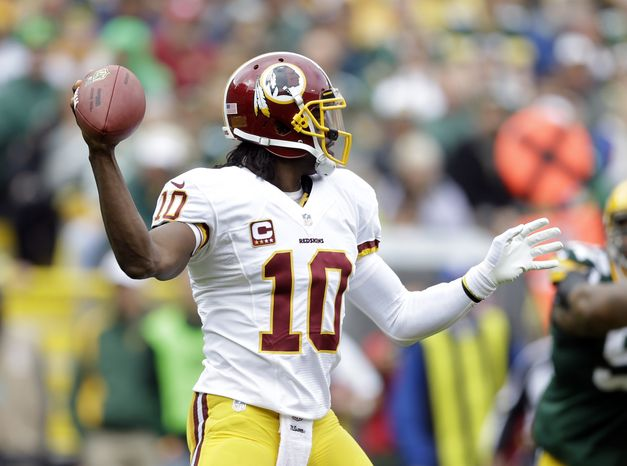 Washington Redskins' Robert Griffin III drops back to pass during the first half of an NFL football game against the Green Bay Packers Sunday, Sept. 15, 2013, in Green Bay, Wis. (AP Photo/Tom Lynn)
