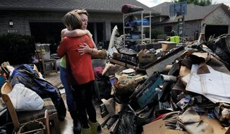 Homeowner Chris Ringdahl is comforted by family friend Katherine MacIntosh in front of her possessions as they clean up from the floodwaters in Longmont, Colo., on Monday. Floodwaters have affected a 4,500-square-mile section of the state, inundating entire neighborhoods and destroying bridges and roads. Officials turned thoughts to rebuilding. (associated press)