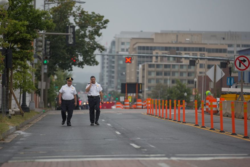 Two police officers walk down M st. outside of the Navy Yard. Recreation centers and parks in the area also closed as police, reporters and onlookers snarled traffic. (Andrew S Geraci/The Washington Times)