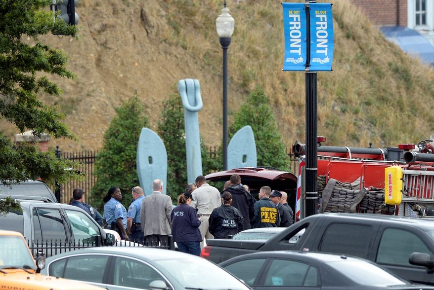 Law enforcement personnel gather outside the gate of  the Navy Yard  on Monday. Law enforcement sources say that by the time the ATF arrived, local police had fatally shot a suspect. The Naval Criminal Investigative Service soon took over, the sources said, but as fatalities were confirmed, the FBI became the lead agency. FBI spokesmen did not respond to calls and emails. (Associated Press)