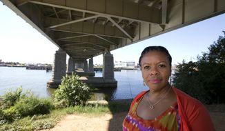 """Alesia Tisdall stands for a photograph under the Frederick Douglass Memorial Bridge which spans the Anacostia River in Washington on Friday, Sept. 6, 2013. Tisdall, who drove daily over the bridge for 15 years but now crosses it only occasionally, said she found it unnerving that the bridge would """"bounce"""" in the middle as she sat in bumper-to-bumper traffic. (AP Photo/Alex Brandon)"""
