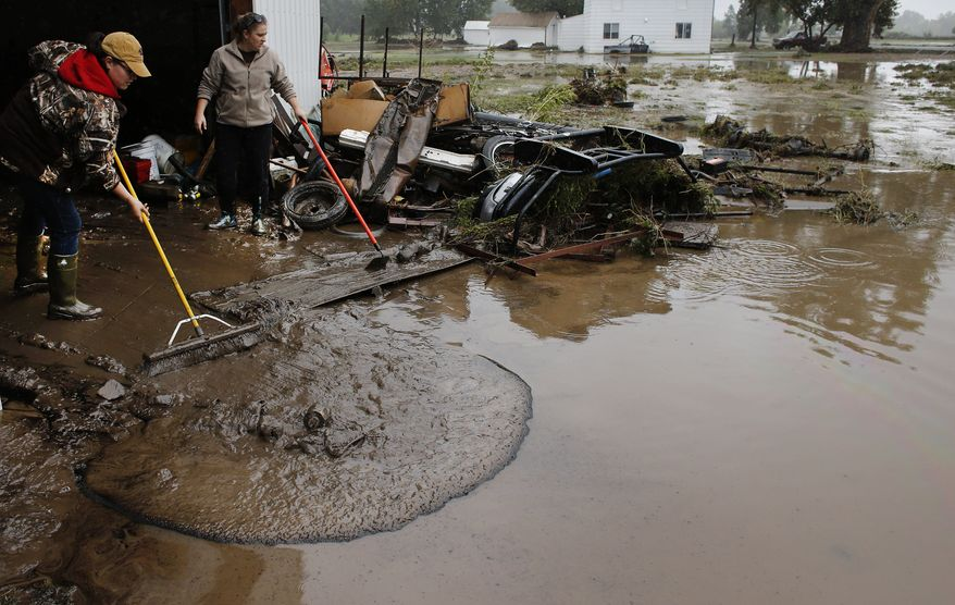 ** FILE ** Genevieve Marquez (left) and Miranda Woodard help salvage and clean property in an area inundated after days of flooding in Hygeine, Colo., on Monday, Sept. 16, 2013. (AP Photo/Brennan Linsley)