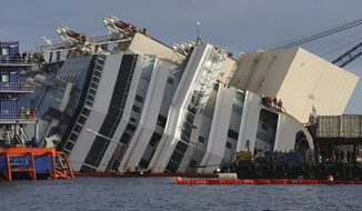 Workers watch the operations on the Costa Concordia ship, lying on its side on the Tuscan Island of Giglio, Italy, Monday, Sept. 16, 2013. An international team of engineers is trying a never-before attempted strategy to set upright the luxury liner, which capsized after striking a reef in 2012 killing 32 people. (AP Photo/Andrea Sinibaldi, Lapresse)