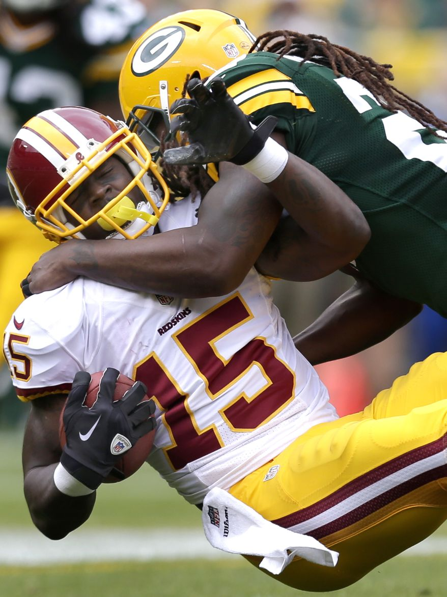 Green Bay Packers' Jerron McMillian, right, tackles Washington Redskins' Josh Morgan following a reception in an NFL football game Sunday, Sept. 15, 2013, in Green Bay, Wis. (AP Photo/The Post-Crescent, Williem Glasheen) NO SALES
