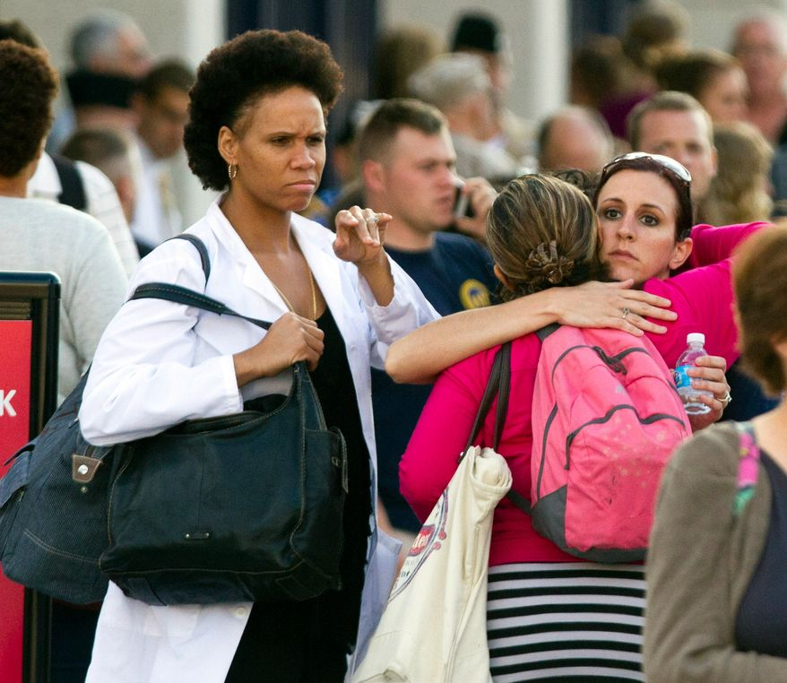 Family and friends greet staff of the Naval Sea Systems Command headquarters after they were bused from the Washington Navy Yard to Nationals Park, in Washington, Monday, Sept. 16, 2013. At least one gunman launched an attack inside the Washington Navy Yard, spraying gunfire on office workers in the cafeteria and in the hallways at the heavily secured military installation in the heart of the nation's capital, authorities said. (AP Photo/Jacquelyn Martin)