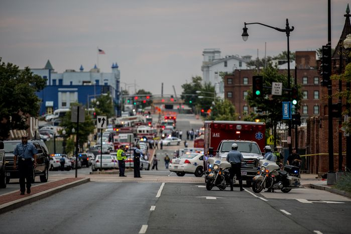 Swarms of police stand outside the Navy Yard as workers are evacuated from the area as police search for a gunman, in Washington, D.C.,  Monday, Sept. 16, 2013. (Andrew S. Geraci/The Washington Times)