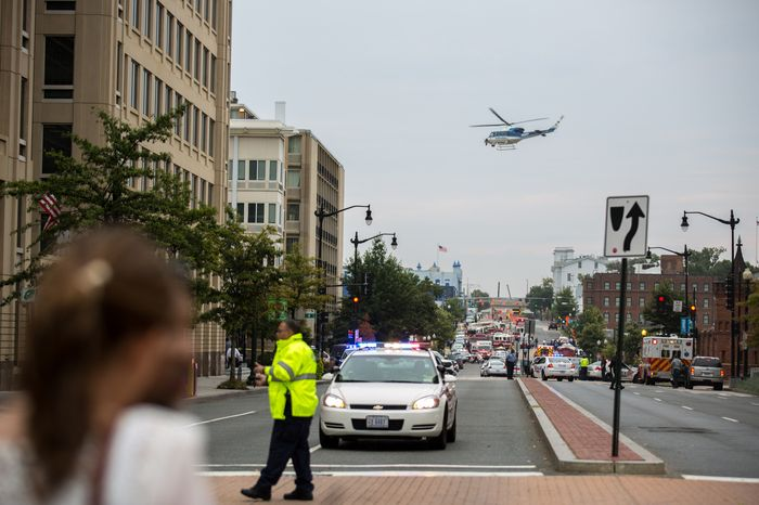A helicopter circles over police outside the Washington Navy Yard as workers are evacuated from the area and police search for a gunman on Monday, Sept. 16, 2013. (Andrew S. Geraci/The Washington Times)