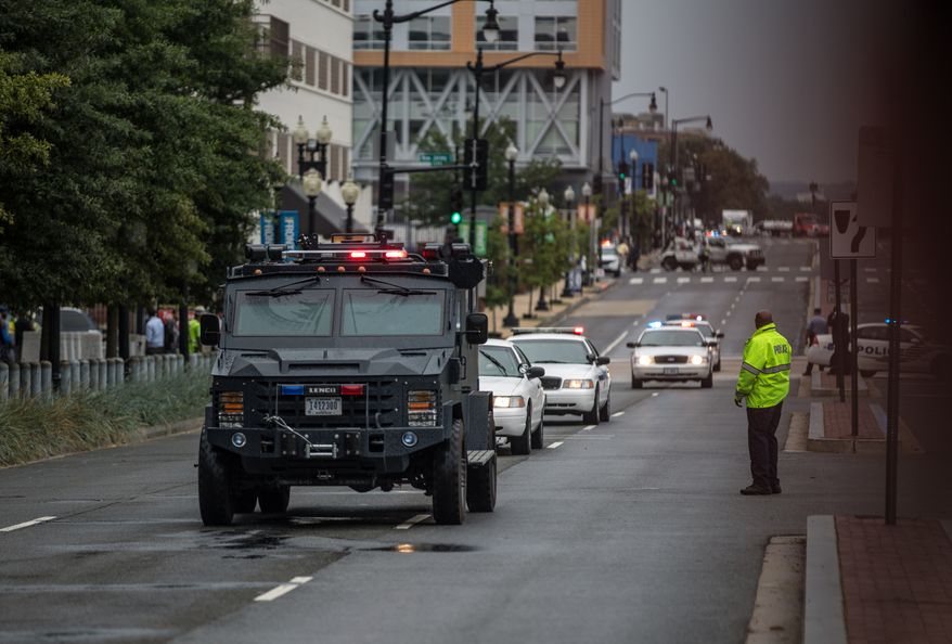 A S.W.A.T. team arrives outside of the Navy Yard as workers are evacuated from the area while police search for a gunman, in Washington, D.C.,  Monday, Sept. 16, 2013.  (Andrew S. Geraci/The Washington Times)