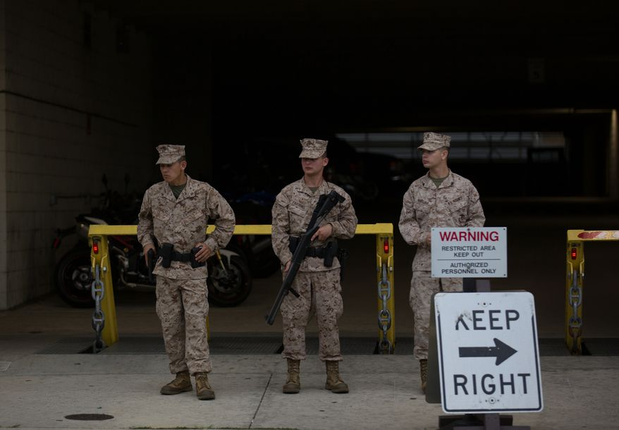 U.S. Marines stand guard with weapons drawn outside the Washington Navy Yard on Monday, Sept. 16, 2013.  (Andrew S. Geraci/The Washington Times)