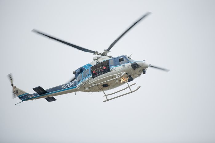 ** FILE ** A rifleman sits inside a helicopter circling above the Washington Navy Yard as police search for shooters on Monday, Sept. 16, 2013. (Andrew S. Geraci/The Washington Times)