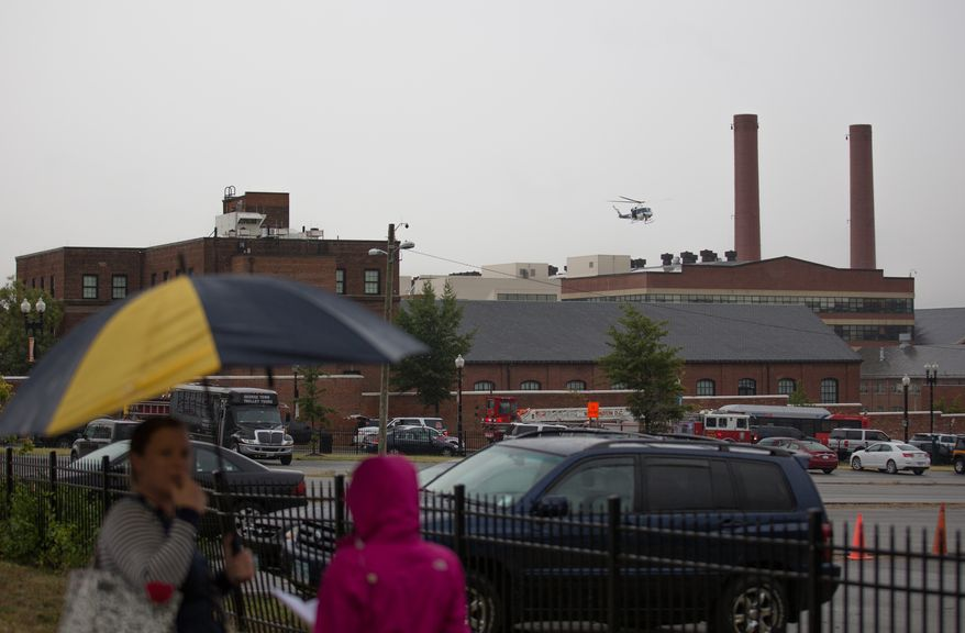 A helicopter circles above the Washington Navy Yard as police search for shooters on Monday, Sept. 16, 2013.  (Andrew S. Geraci/The Washington Times)