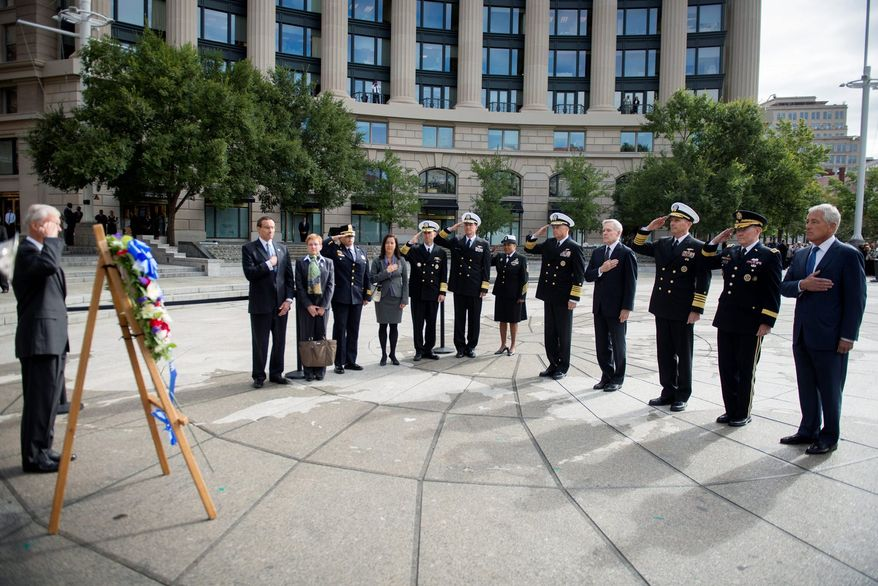Secretary of Defense Chuck Hagel (right) along with Gen. Martin E. Dempsey, chairman of the Joint Chiefs of Staff; Adm. Jonathan Greenert, chief of Naval Operations; Ray Mabus, Secretary of the Navy; and Adm. James A. Winnefeld Jr., vice chairman of the Joint Chiefs of Staff, render honors Tuesday during a wreath-laying ceremony at the U.S. Navy Memorial. (U.S. Navy via Associated Press)