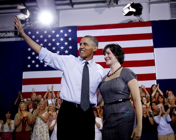 **FILE** President Obama, accompanied by Sandra Fluke, waves at a campaign event at the University of Colorado Auraria Events Center in Aurora, Colo., on Aug. 8, 2012. Fluke is a Georgetown law student who inadvertently gained notoriety when talk show host Rush Limbaugh spoke disparagingly of her testimony before Congress on the issue of contraception and insurance coverage. (Associated Press)