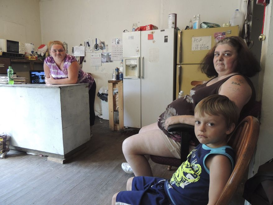 **FILE** Renee Adams (left) poses with her mother, Irene Salyers, and son, Joseph, 4, at their produce stand in Council, Va., on July 12, 2013. Four out of five U.S. adults struggle with joblessness, near poverty or reliance on welfare for at least parts of their lives, a sign of deteriorating economic security and a vanishing American Dream amid rising incidences of hardship among whites. (Associated Press)
