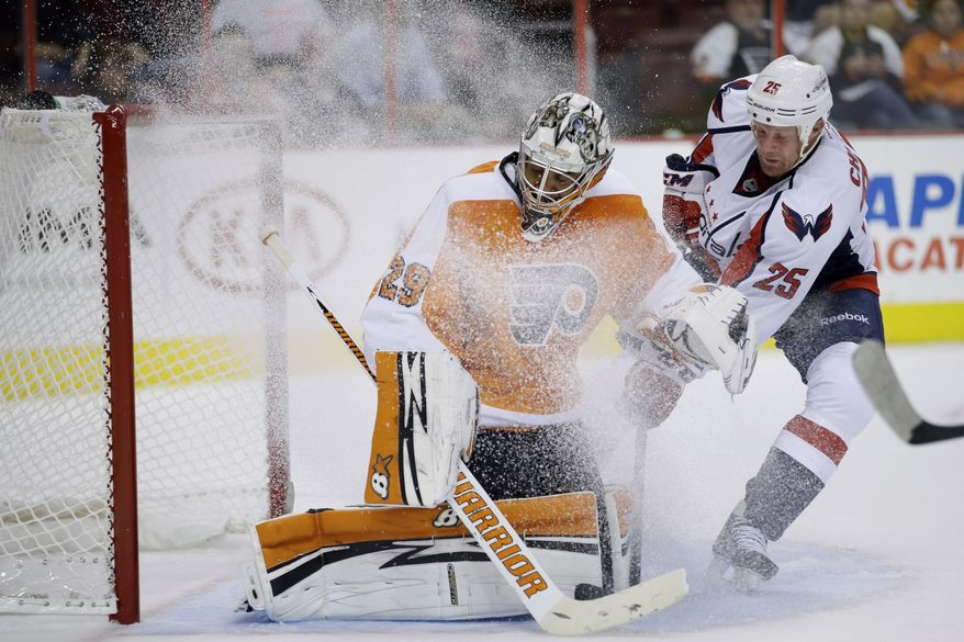 Philadelphia Flyers goalie Ray Emery, left, blocks a shot as Washington Capitals' Jason Chimera slides in during the first period of a preseason NHL hockey game, Monday, Sept. 16, 2013, in Philadelphia. (AP Photo/Matt Slocum)