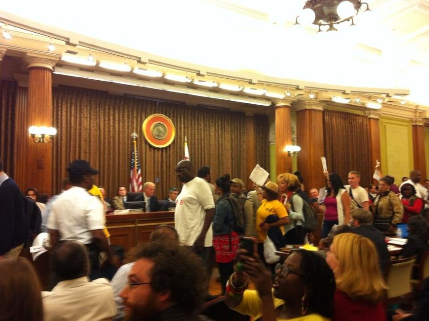 "Protesters exit the D.C. Council chambers after members failed to override the mayor's veto of the ""living wage"" bill. (Andrea Noble/The Washington Times)"