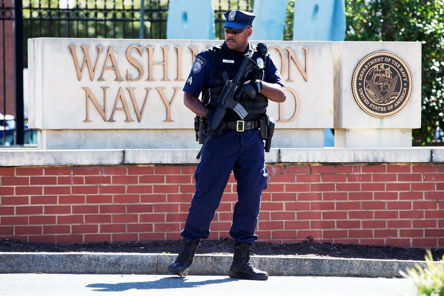 ** FILE ** Under heavy guard: The Washington Navy Yard was closed to all but essential personnel on Tuesday, Sept. 17, 2013, the day after a gunman launched an attack that hit office workers in the cafeteria and in the hallways at the military installation. (Associated Press)