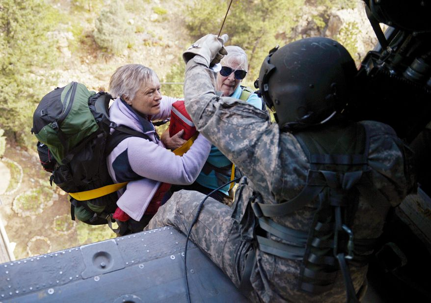 Two women are hoisted into a Blackhawk helicopter as they are rescued near Jamestown, Colo., on Tuesday, Sept. 17, 2013, during a helicopter search of the area devastated by flooding. (AP Photo/Denver Post, Joe Amon, Pool)