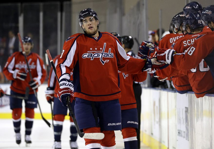 Washington Capitals right wing Tom Wilson high-fives teammates after scoring a goal in the first period of a preseason NHL hockey game against the Boston Bruins, Tuesday, Sept. 17, 2013, in Baltimore. (AP Photo/Patrick Semansky)