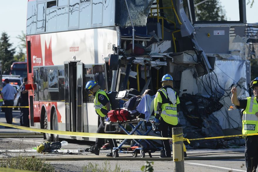 A bus passenger is taken to an ambulance following a collision between a Via Rail train and city transit bus in Ottawa's west end on Wednesday, Sept. 18, 2013. (AP Photo/The Canadian Press, Adrian Wyld)